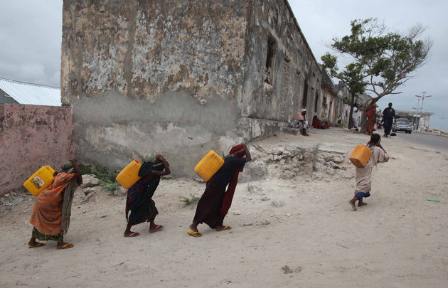 Internally displaced women carry jerry-cans of water on their backs from a well in Somalia's capital Mogadishu